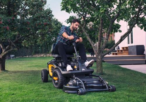 Homme utilisant une tondeuse autoportée sur son jardin