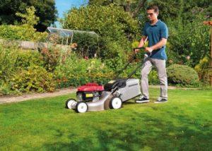 Homme en train de tondre sa pelouse avec le modèle Honda Izy HRG416 PK